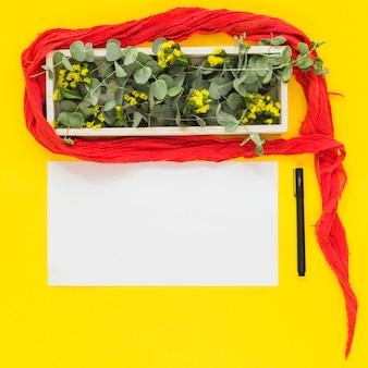 Rote kleidung um die holzkiste; stift und leeres weißbuch auf gelbem hintergrund