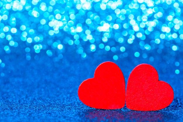 Rote kleine dekorative herzen gegen blau funkelnden glitzer mit erstaunlichen bokeh-lichtern.