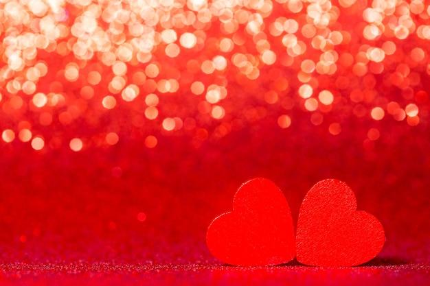 Rote kleine dekorative herzen gegen rotes glitzern mit erstaunlichen bokeh-lichtern
