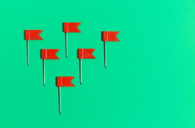 Rote kleine flaggenstifte auf grünem hintergrund. sicht von oben .