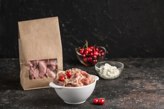 Rote knödel mit kirschen in einer schüssel und umweltfreundliche papierverpackung für die lieferung mit weißer sauce