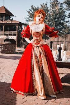Rote königin im schloss. rothaarige frau in einem schicken vintage-kleid. modefoto