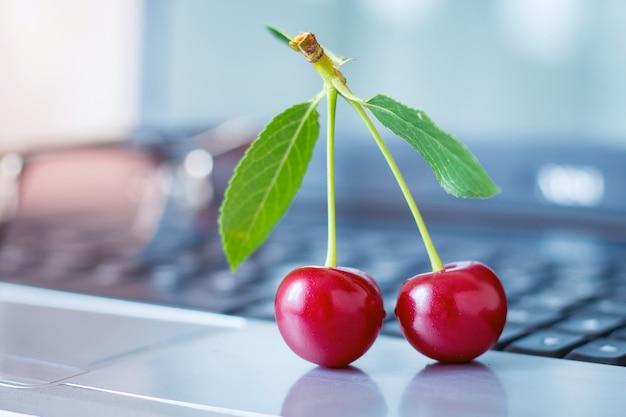 Rote köstliche kirschbeeren und gläser auf einem laptop