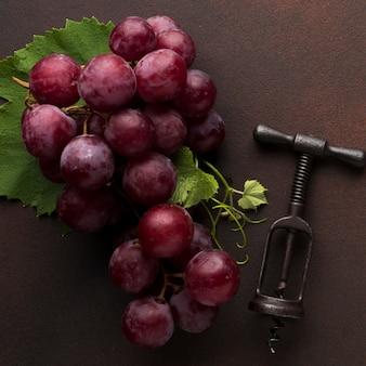 Rote köstliche trauben und korkenzieher