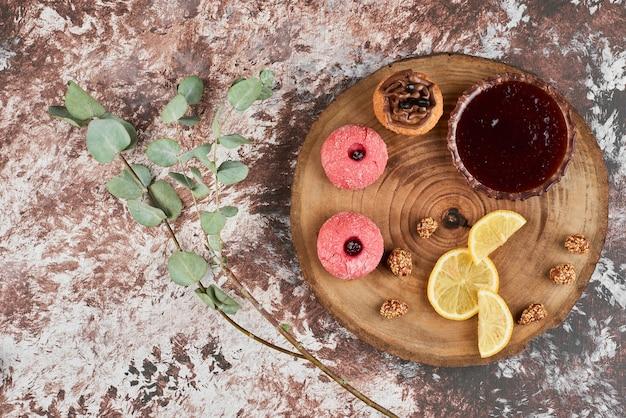Rote konfektion und kekse auf einem holzbrett.