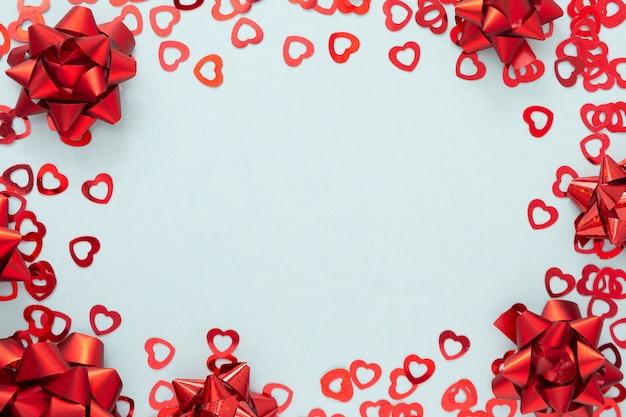 Rote konfettis der herzform und rote bandboes, valentinstag