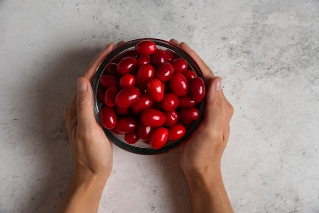 Rote kornelkirschen in der glasschale in der hand einer person.