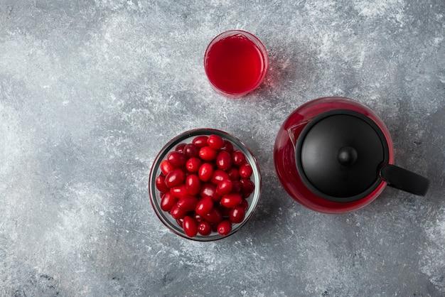 Rote kornelkirschen in einer glasschale mit saft im wasserkocher und im glas.