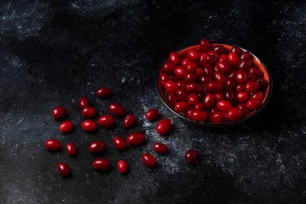 Rote kornelkirschen in einer tasse auf schwarzer oberfläche.