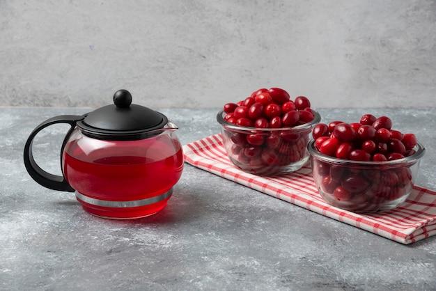 Rote kornelkirschen in glasbechern mit einem kessel saft.