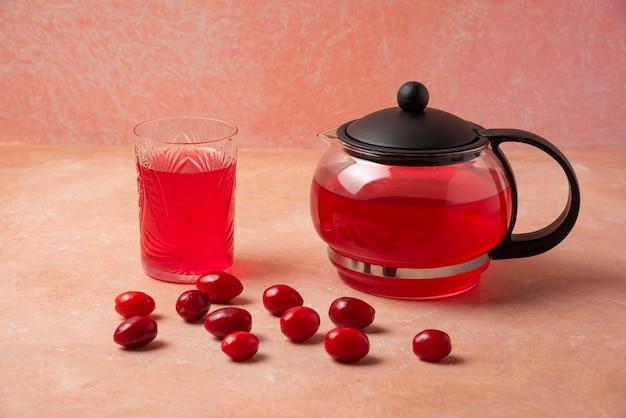 Rote kornelkirschen mit saft im wasserkocher und im glas.