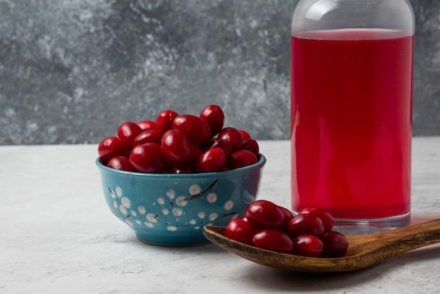 Rote kornelkirschen und ein glas getränk.
