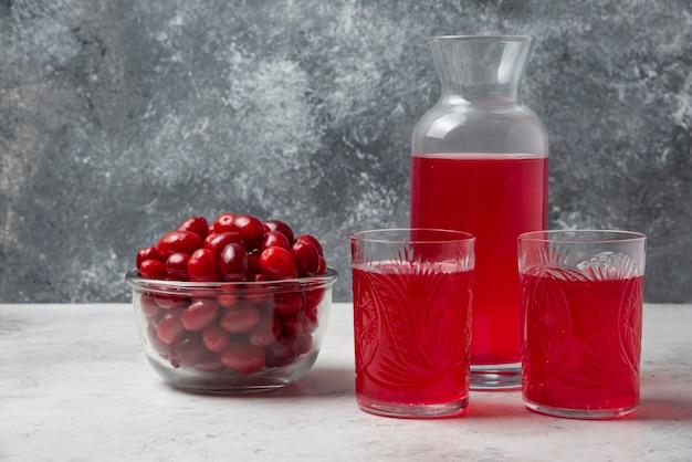 Rote kornelkirschenbeeren in einer glasschale mit saft beiseite.