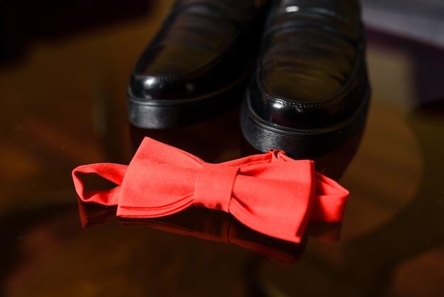 Rote krawatte des schmetterlinges und schwarze schuhe.
