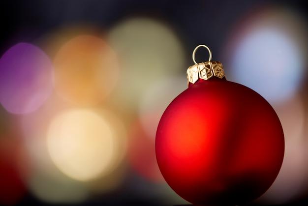 Rote kugel über unscharfem lichthintergrund. weihnachts- und neujahrsdekoration.