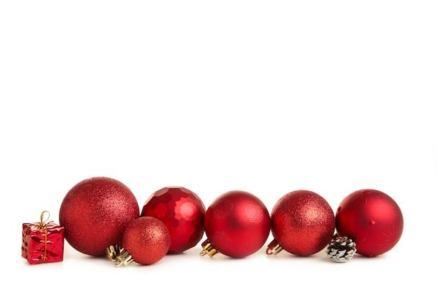 Rote kugeln mit weihnachtsdekoration auf weißem hintergrund.