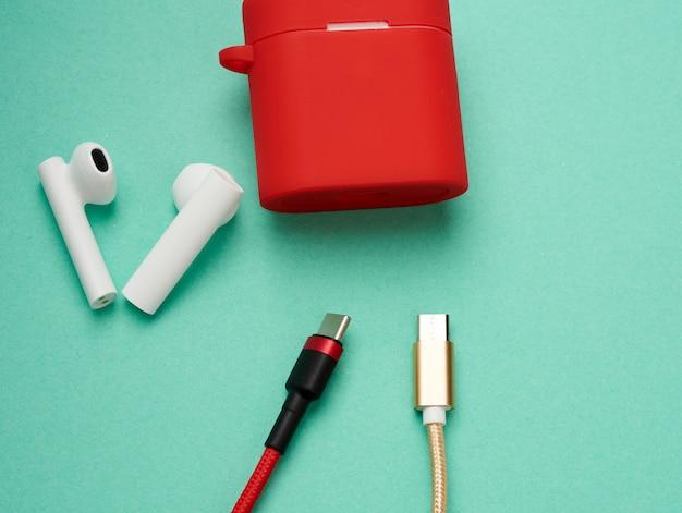 Rote ladebox für kopfhörer und klebt kopfhörer auf eine grüne oberfläche