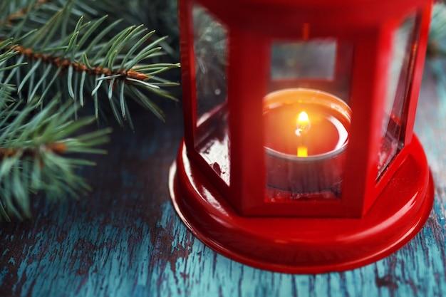 Rote laterne mit einer brennenden kerze nach innen und einem weihnachtsbaum