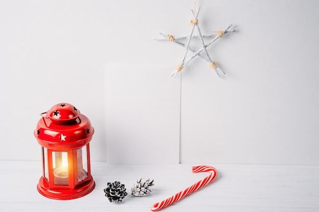 Rote laterne mit einer kerze, kiefernkegeln, einem stern und einem leeren weißen blatt auf einem weißen hintergrund. weihnachtsdekoration