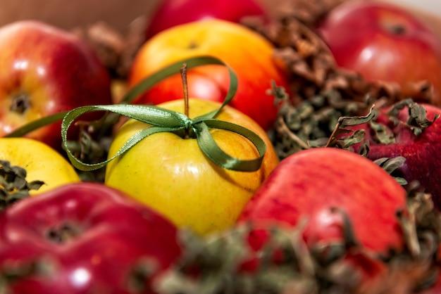 Rote, leckere äpfel nahaufnahme auf einem hintergrund des grünen mooses, geschenkdekoration mit grünem band