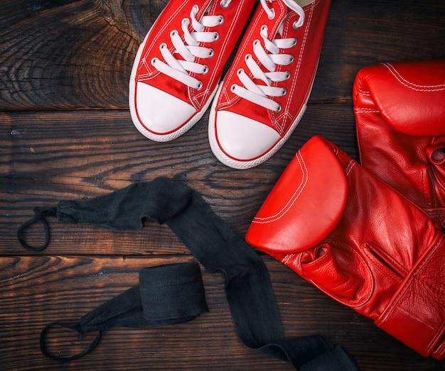 Rote leder boxhandschuhe und textil turnschuhe