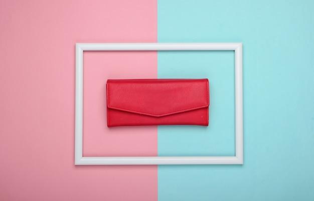 Rote lederbrieftasche in einem weißen rahmen auf rosa blauer oberfläche