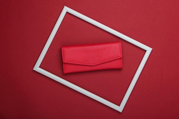 Rote lederbrieftasche in einem weißen rahmen auf roter oberfläche