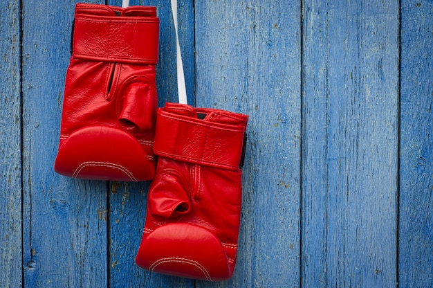 Rote lederne boxhandschuhe, die an einem seil hängen