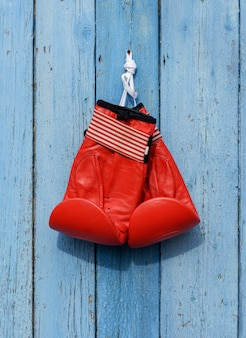 Rote lederne boxhandschuhe hängen an einem nagel