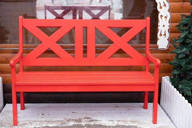 Rote, leere holzbank draußen im winter.