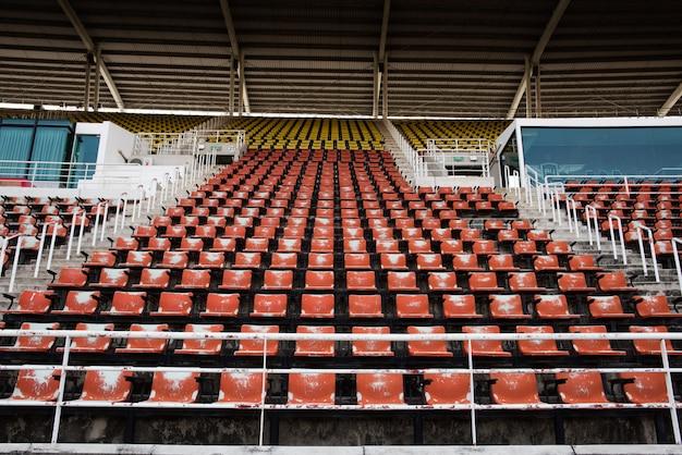 Rote leere und alte plastiksitze im stadion.