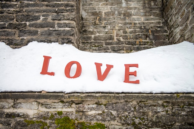 Rote liebesbriefe im schnee. wort liebe auf weißem hintergrund über valentinstag freunde oder liebhaber tag