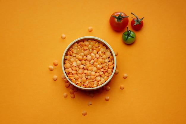 Rote linsen in einer runden holzschale auf einem orangefarbenen hintergrund und kirschtomaten Premium Fotos