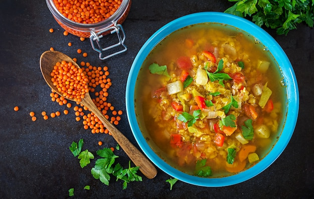 Rote linsensuppe auf dunkler tabelle. gesundes essenkonzept. veganes essen. ansicht von oben. flach liegen
