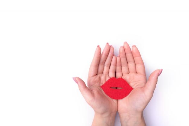 Rote lippen der fashionrt-porträtfrau küssen in ihrer hand mit einem hellen kontrastierenden make-up.