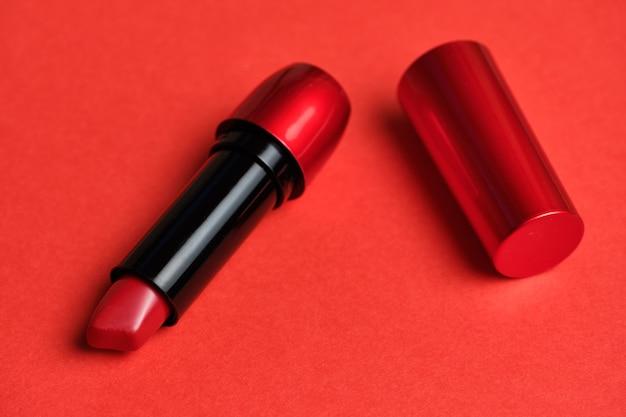 Rote lippen des kosmetischen lippenstifts auf einem roten hintergrund.