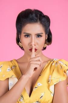 Rote lippen und finger der asiatischen frau der schönheit, die stillezeichen zeigt