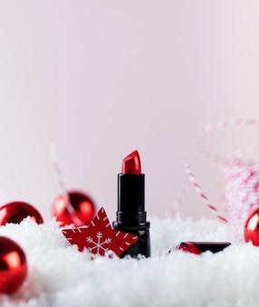 Rote lippenstifttube und christbaumkugeln auf künstlichem schneehaufen