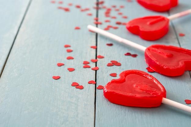 Rote lutscher mit herzform auf blauer holzoberfläche lieben konzept valentinstag.