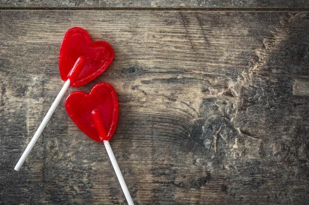 Rote lutscher mit herzform auf holzoberfläche liebeskonzept valentinstag.