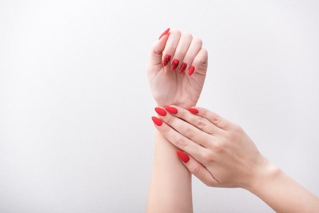 Rote maniküre mit einem muster. weibliche hände auf einem weiß
