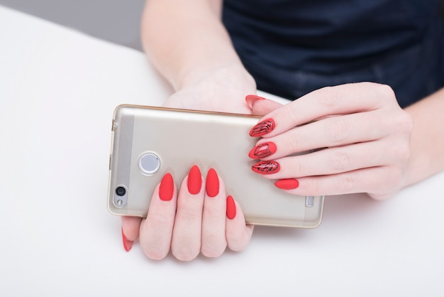 Rote maniküre. smartphone in weiblicher hand.