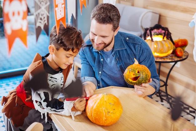 Rote markierung. junge, der skelettkostüm hält, das roten marker hält, während kürbis für halloween-familienfeier färbt