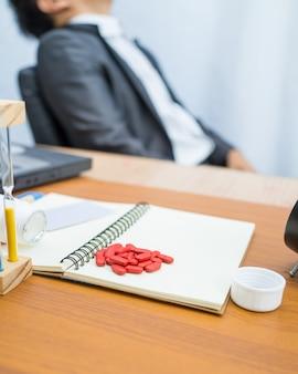 Rote medizin auf notizbuch mit hölzerner mustertabelle auf unscharfem sitzendem stuhl des geschäftsmannes,