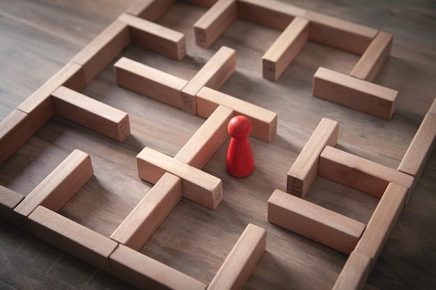 Rote menschliche figur, die im labyrinth steht.