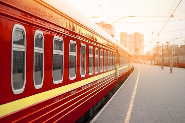 Rote metallzugbahnwagen mit fenstern auf einem bahnsteig im sonnenuntergangslicht.