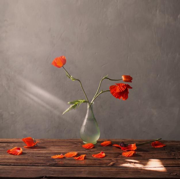Rote mohnblumen in der vase auf holztisch