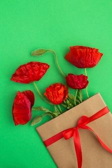 Rote mohnblumen in einem umschlag gebunden mit einem roten band auf der grünen oberfläche. frühlings- oder sommerblumenkonzept.