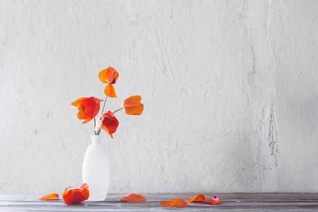 Rote mohnblumen in weißer vase auf weißem hintergrund