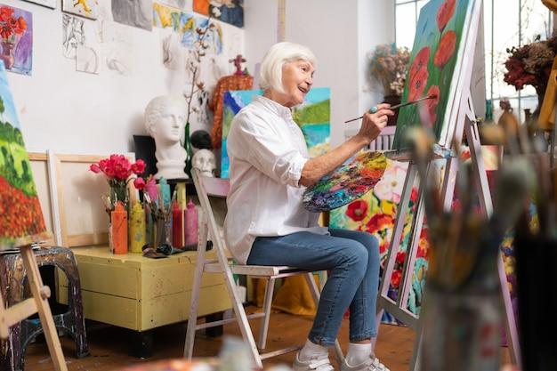 Rote mohnblumen malen. alter künstler, der sich wirklich zufrieden fühlt, während er rote mohnblumen malt, die in der nähe der staffelei sitzen
